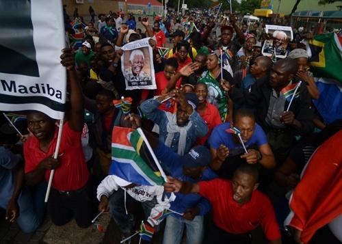 Người Nam Phi giương cờ, ảnh Mandela để tỏ lòng thành kính cố lãnh đạo.