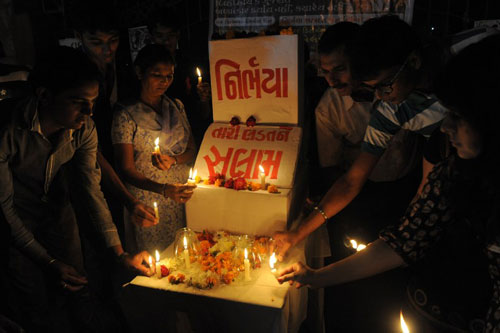 [Caption]Indian students and activists light candles during a memorial ahead of the one-year anniversary of a gang-rape and murder of a 23-year-old physiotherapy student that sparked massive protests in the Indian capital, outside Vastrapur Lake in Ahmedabad on December 14, 2013. The savage attack spurred intense debate about the way India treats its women, and led to a stiffening of punishments for sexual abuse. Ảnh:AFP