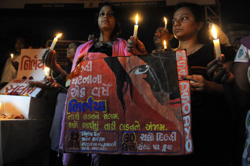 [Caption]ndian students and activists hold placards and candles during a memorial ahead of the one-year anniversary of a gang-rape and murder of a 23-year-old physiotherapy student that sparked massive protests in the Indian capital, outside Vastrapur Lake in Ahmedabad on December 14, 2013.