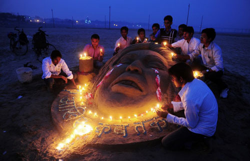 [Caption]Indian students make a sand sculpture to pay homage as they commemorate the first anniversary of the fatal gang rape of the 23-year-old New Delhi student on a moving bus, in Allahabad on December 16, 2013