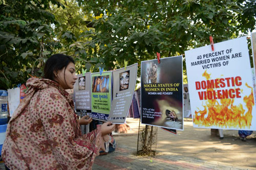 [Caption]An Indian woman looks at posters exhibited during a program commemorating the December 2012 fatal gang-rape of a 23-year old New Delhi student, in Ahmedabad on December 16, 2013.