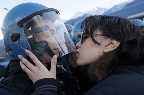 [Caption]A demonstrator kissed a police officer during a protest Nov. 16 in Susa, Italy, against a high-speed train line between Lyon, France, and Turin, Italy. Marco Bertorello/AFP