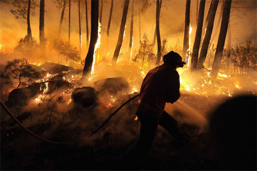 [Caption]A firefighter was silhouetted against flames as crews battled a forest fire in Moimenta da Beira, Portugal, Aug. 2.Nuno Andre Ferreira/European Pressphoto Agency