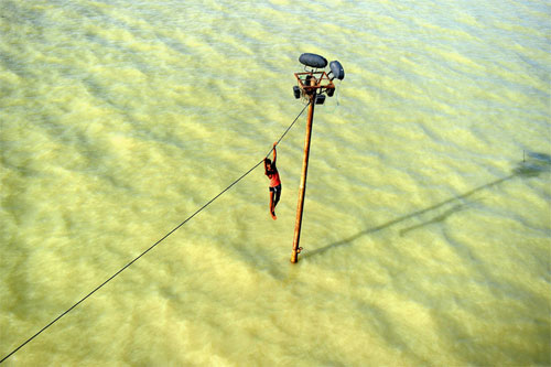 [Caption]A youth held on to a power line as monsoon floodwaters from the overflowing Ganges rose in Allahabad, India, Aug. 6.Sanjay Kanojia/Agence France-Presse/Getty Images