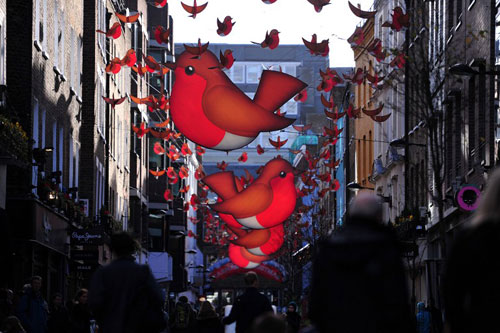 [Caption]Shoppers walk under Christmas decorations in central London on December 22, 2013.