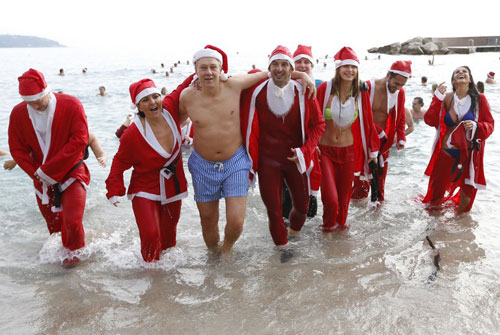 [Caption]People dressed as Santa Claus enjoy a traditional Christmas bath on December 22, 2013 in Monaco.