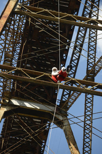 [Caption]Guatemalan municipal firefighter Carlos Chacon, dressed as Santa Claus, goes down a cable from a bridge to deliver presents to children in Guatemala City on December 22, 2013.