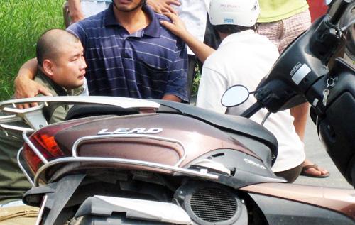 Anh Quang ngồi ôm thi thể vợ nằm bên cạnh xe máy. Ảnh: An Nhơn