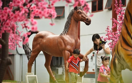 Trẻ em chơi trước tượng ngựa tại thủ đô Kuala Lumpur. Ảnh: Xinhua