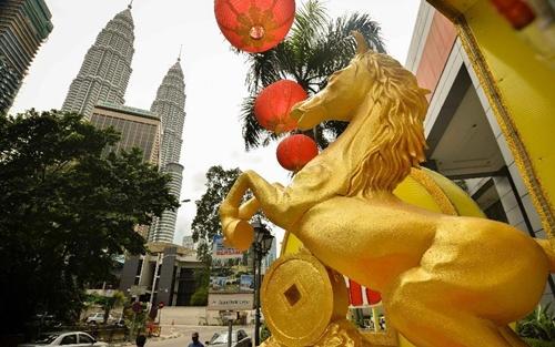 """Hình ngựa lấp lánh ánh vàng gần tháp đôi Petronas, một biểu tượng của thành phố. Henry Saw, một người mua sắm cho biết năm Ngựa sẽ là một năm thành công với những người làm việc chăm chỉ. """"Ngựa có thể phi nước đại rất nhanh và giống chúng tôi, đây là cơ hội để chúng ta làm việc chăm chỉ và mau lẹ trong suốt năm để được thịnh vượng và thành công"""", ông nói. Ảnh: Xinhua"""