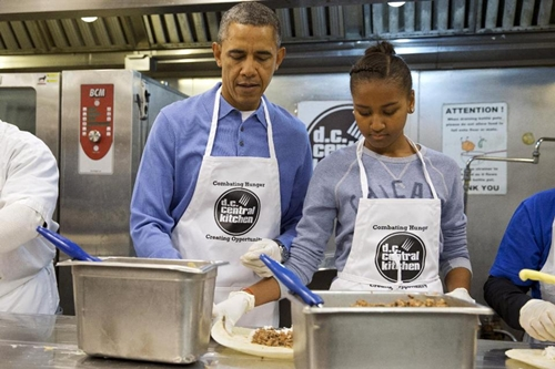 Tổng thống Obama cùng con gái Sasha tham gia dây chuyền làm bánh burrito ở DC Central Kitchen. Ảnh: AP.