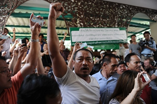 Người dân Thái Lan giơ cao chứng minh thư nhân dân Frustrated Thai voters hold their national identification cards and shout at police blocking the entrance to a polling station as voting was cancelled after anti-government protesters prevented the delivery of election material in downtown Bangkok on February 2, 2014