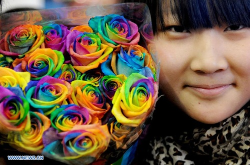A consumer shows a bouquet of seven-color roses in Shenyang, capital of northeast China's Liaoning Province, Feb. 10, 2014