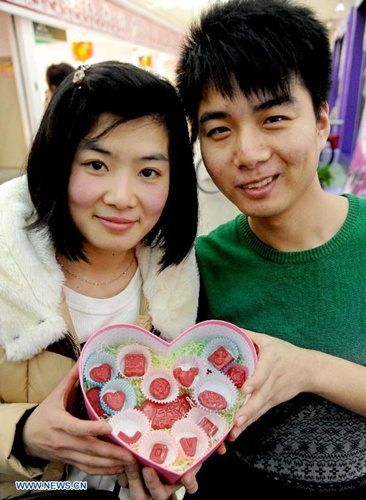 A couple show their handmade chocolates for Valentine's Day in Shenyang, capital of northeast China's Liaoning Province, Feb. 10, 2014. As the Valentine's Day approaches, various commodities for lovers are welcomed among consumers. (Xinhua/Zhang Wenkui)