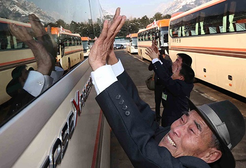 Park Woon-Hwa (R) of North Korea waves goodbye to his South Korean relatives. Photo by Lee Ji-Eun/EPA/South Korea Out