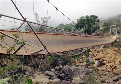 Cầu treo bị đất dây cáp và đổ nghiêng, khiến hàng chục người bị lao xuống suối. Ảnh: Sơn Thủy