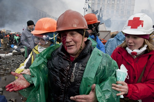 A wounded anti-government protester is evacuated during clashes with riot police on Kiev