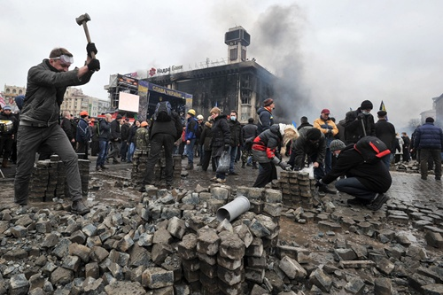 Protesters dig up cobblestones to use them against riot police on Kiev
