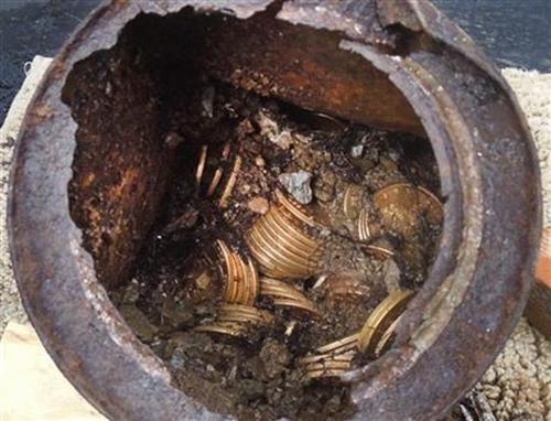 Một trong số 8 hộp kim loại gỉ chứa đồng xu vàng được tìm thấy. Ảnh: AP.