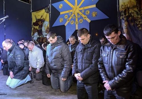 Cảnh sát chống bạo động quỳ gối xin lỗi người dân ở thành phố Lviv. Ảnh: Reuters.