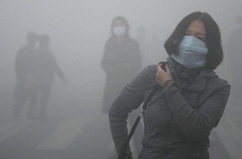 Người dân đeo khẩu trang đi trong màn khói mù ở Cáp Nhĩ Tân, Trung Quốc. Ảnh:Kyodo News