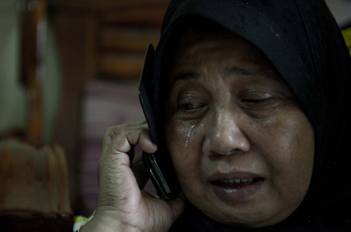 [Caption]pur : A relative of Norliakmar Hamid and Razahan Zamani, passengers on a missing Malaysia Airlines Boeing 777-200 plane, cries at their house in Kuala Lumpur on March 8, 2014.