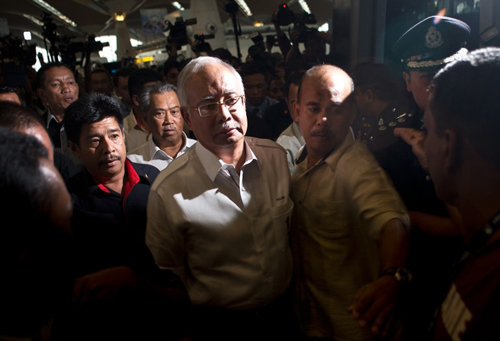 [Caption]Malaysian Prime Minister Najib Razak (C) arrives to meet family members of missing passengers at the reception centre at Kuala Lumpur International Airport on March 8, 2014.