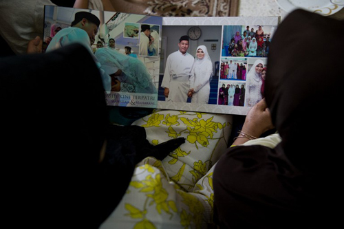 [Caption]amily members look at a wedding album of Norliakmar Hamid (R, in veil) and Razahan Zamani, passengers on a missing Malaysia Airlines Boeing 777-200 plane in Kuala Lumpur on March 8, 2014.