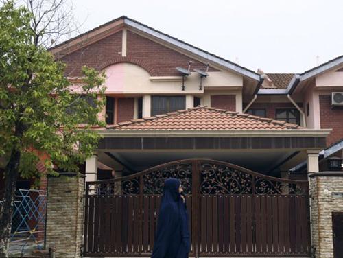 Một người phụ nữ đi ngang nhà của phi công phụFariq Abdul Hamid in Shah Alam ở ngoại ô Kuala Lumpur. Ảnh: AP