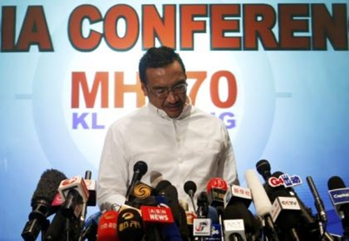 Malaysia's acting Transport Minister Hishammuddin Hussein reads a statement during a news conference about the missing Malaysia Airlines flight MH370, at Kuala Lumpur International Airport