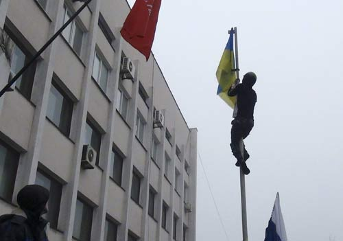 [Caption]A man climbs up a post to remove a Ukrainian flag as protesters hold a rally outside the mayor's office in Mariupol, April 13, 2014. Separatist protesters on Sunday seized control of the mayor's office in the town of Mariupol, eastern Ukraine, on the Azov Sea, local media said. The protesters entered the building following a rally involving about 1,000 people demonstrating in favor of the creation of a separate republic in eastern Ukraine, a local journalist for the newspaper Priazovsky Worker said. REUTERS/