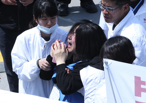 A mother, center, of a passenger aboard the sunken ferry Sewol in the water off the southern coast cries after confirming her daughter's name on the list of the victims found dead at a port in Jindo, South Korea, Wednesday, April 23, 2014. The grim work of recovering bodies from the submerged South Korea ferry proceeded rapidly Wednesday, with the official death toll reaching more than 140, though a government official said divers must now rip through cabin walls to retrieve more victims. (AP Photo/Ahn Young-joon)