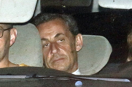 Former French President Nicolas Sarkozy (C) arrives with police by car at the financial investigation unit in Paris to be presented to a judge late July 1, 2014