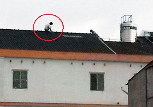 Tên trộm cố thủ trên nóc nhà, dọ sẽ nhảy xuống tự tự nếu ai đó tiếp cận bắt. Ảnh: Độc giả cung cấp