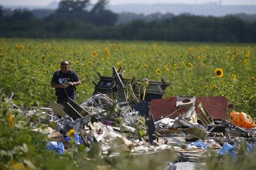 Điều tra viên của Malaysia kiểm tra hiện trường MH17. Ảnh: Reuters.