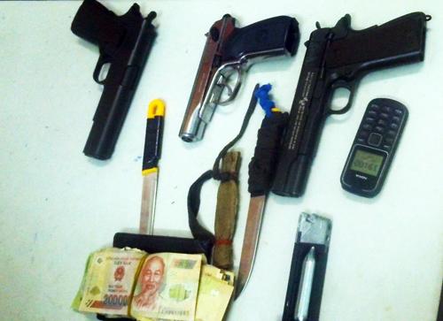 3 khẩu súng ngắn cùng những tang vật liên quan của nhóm cướp bị thu giữ. Ảnh: Hoàng Trường