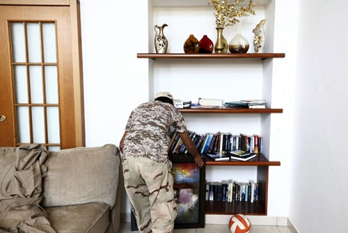 A member of the Fajr Libya (Libya Dawn) Islamist militia holds a picture at the living room of a villa at the US diplomatic compound in the Libyan capital Tripoli, on August 31, 2014, after members of the group moved into the complex of several villas in southern Tripoli to prevent it from being looted, according to the faction.