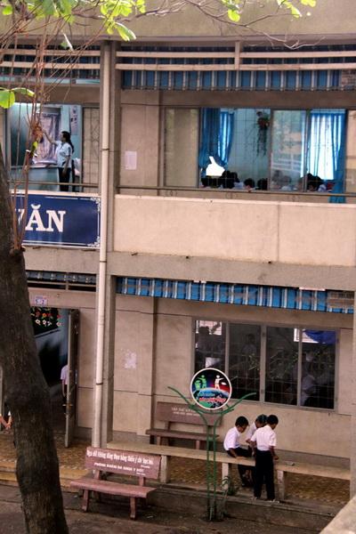 Trong lúc học sinh ca chiều nô đùa ở sân trường thì lớp học giữa trưa ở trường tiểu học Phan Chu Trinh vẫn dạy và học. Ảnh: Hoàng Trường