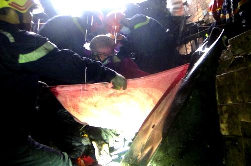 Lính cứu hộ dùng mền quấn nạn nhân để đưa ra ngoài. Ảnh: