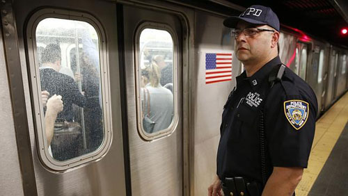 [Caption]A US police officer watches a train pull out of the Times Square subway station in New York. Picture: AP Photo/Seth Wenig. Source: AP