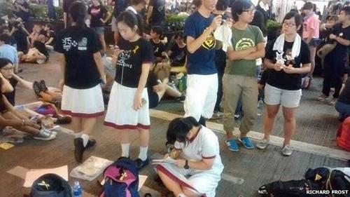 Cuộc biểu tình đang diễn ra ở Hong Kong được cho là dữ dội nhất trong kể từ khi nơi này trở về với Trung Quốc năm 1997. Làn sóng biểu tình ủng hộ dân chủ do các nhóm học sinh, sinh viên tổ chức. Tuy nhiên, một số sinh viên vẫn không quên nhiệm vụ học tập và tranh thủ làm bải tập về nhà ngay khi có thể. Ảnh: BBC.