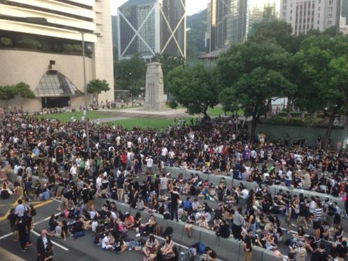 """Không dẫm lên cỏ  Bức ảnh đăng tải trên tở SCMP cho thấy người biểu tình tập trung rất đông tại một đài tưởng niệm Hong Kong. Tuy nhiên, đám đông vẫn tuân thủ các biển báo ở đây, không dẫm lên bãi cỏ. """"Dù tập trung rất đông ở đài tưởng niệm chiến tranh tại khu Trung tâm nhưng không mộ ai đứng hay ngồi lên cỏ"""", tờ báo viết. Ảnh: SCMP."""