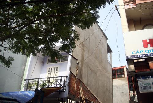 Căn nhà 3 tầng (trái) bị nghiêng sang phần công trình đang thi công. Ảnh: An Nhơn