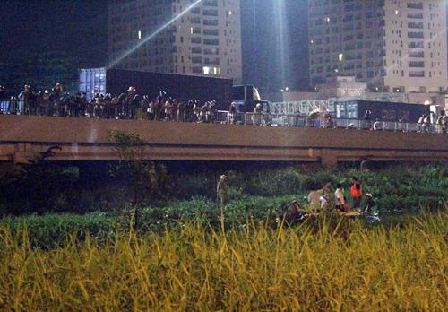 Hàng trăm người dân hiếu kỳ đứng trên cầu Sài Gòn và đường Trần Não theo dõi. Ảnh: Châu Thành