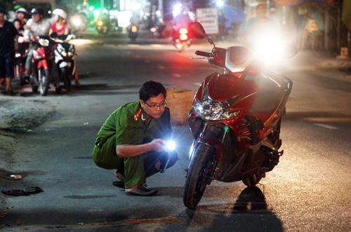 Công an tìm dấu vết trên xe máy của nạn nhân. Ảnh: An Nhơn
