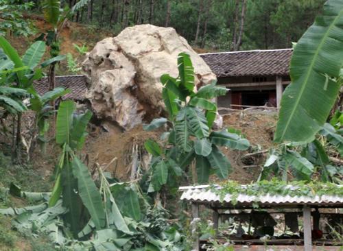 Tảng đá khổng lồ nằm giữa sân nhà anh Tuyền như một hòn non bộ khủng. Ảnh: Báo Cao Bằng.