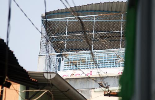 Tầng sân thượng mà nghi can được cho là treo lên lưới sắt và nhảy qua nóc nhà bên cạnh. Tấm bạt còn dính máu. Ảnh: An Nhơn