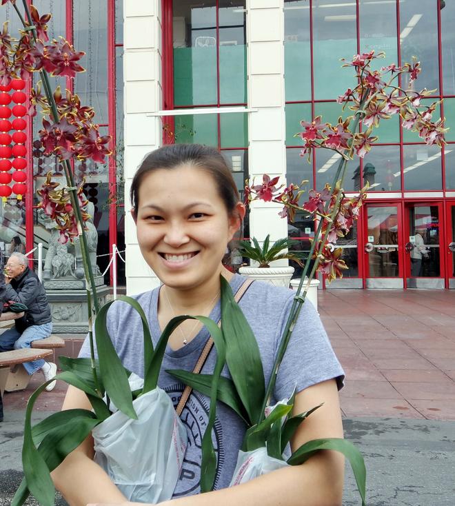 """<p class=""""Normal"""">  Chợ hoa thu hút rất nhiều bà con Việt kiều tới mua sắm, tham quan và chụp ảnh. Trong hình, một phụ nữ Việt khoe hai chậu hoa lan vũ nữ vừa mua với giá 18 USD mỗi chậu.</p>"""