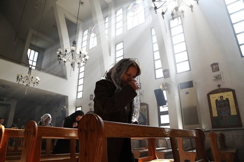 An Assyrian woman attends a mass in solidarity with the Assyrians abducted by Islamic State fighters in Syria earlier this week, inside Ibrahim al-Khalil church in Jaramana, eastern damascus March 1, 2015. Militants in northeast Syria are now estimated to have abducted at least 220 Assyrian Christians this week, a group monitoring the war reported. REUTERS/Omar Sanadiki (SYRIA - Tags: POLITICS CIVIL UNREST CONFLICT RELIGION TPX IMAGES OF THE DAY)