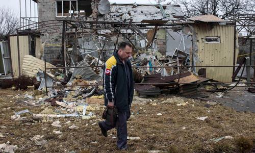 Một người đàn ông đi qua ngôi nhà đổ nát ở Donetsk, miền đông Ukraine hôm nay. Ảnh: Reuters